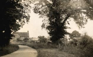 Low Road facing north towards Cuddington, with the farmhouse in the background. The road has changed little over the years
