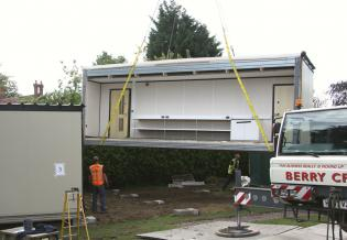 The crane lowers the fourth classroom section for the builders to catch hold