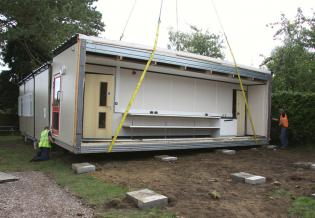 As the crane gently lowers the classroom unit, the builders make sure that it lines up correctly with the other units