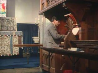 "James Warwick as Bobby Jones, the son of the Vicar, ""playing"" the St Nicholas' Church organ"